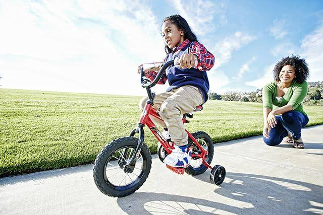 child riding with training wheels